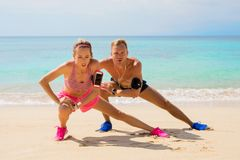 Fitness pals streching after workout on the beach. Fit couple streching after workout on the beach Royalty Free Stock Photos