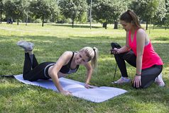 Fitness in the park. The girl on the left has a problem while she does a push-up. And the girl on the right side measures the time on the stopwatch stock photo