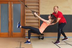 Fitness parners in sportswear doing exercises at gym. Fitness sport gym concept stock photos