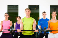 Fitness people with barbell in gym