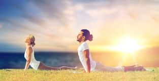 Couple making yoga cobra pose outdoors Stock Images