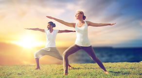Couple making yoga warrior pose outdoors Stock Photo