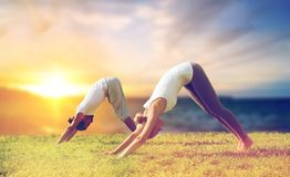 Smiling couple making yoga dog pose outdoors royalty free stock photos