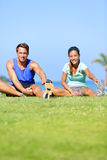 Fitness people - couple stretching exercises stock photography