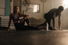 Fitness people doing stretching warmup at gym. Fitness people doing stretching exercise at gym. Young women warming up with fitness trainer at gym Royalty Free Stock Images