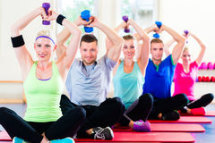 Fitness people in gym working out with dumbbells Royalty Free Stock Photos