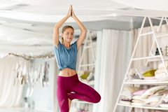 Young woman doing yoga tree pose at studio. Fitness, people and healthy lifestyle concept - young woman doing yoga in tree pose at studio royalty free stock images