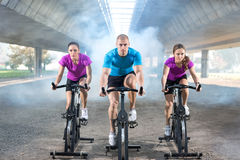 Fitness people riding exercise bikes Royalty Free Stock Photo