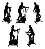 Fitness people. Silhouettes of fitness people on gym bike Stock Photography
