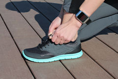 Fitness people using smart watch. Women runner getting ready for jogging. Sport, active lifestyle concept Royalty Free Stock Image