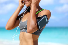 Fitness phone armband woman putting earphones. Fitness phone armband runner woman putting earphones. Closeup of sports smartphone case holder touchscreen strap Royalty Free Stock Photo