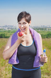 Fitness plus size woman with bottle of water eating apple Stock Image