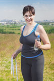 Fitness plus size woman with centimeter and water bottle Royalty Free Stock Image