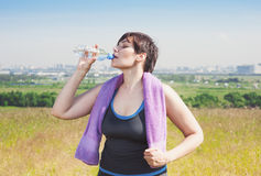 Fitness plus size woman with towel drinking water Royalty Free Stock Photo