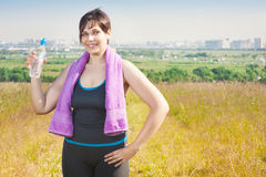 Fitness plus size woman with towel and water bottle Stock Photo