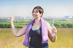 Fitness plus size woman with towel and water bottle Royalty Free Stock Images