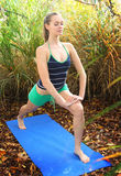 Fitness portrait. Young blond caucasian woman participating in a yoga exercises in the garden. Shallow depth of field, focus is on models face Stock Images