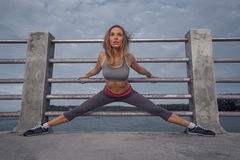 Fitness pretty blonde woman at the harbour in the morning Royalty Free Stock Image