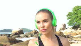 Fitness pretty blonde woman on tropical beach during beautiful summer day. Close up of young pretty blonde female wearing black exercise clothing and bright stock video
