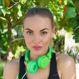 Fitness pretty blonde woman on tropical beach during beautiful summer day. Close up of young pretty fitness female wearing bright green headphones smiling and stock photo