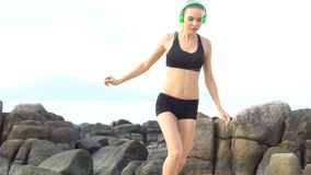 Fitness pretty blonde woman on tropical beach during beautiful summer day. Young pretty blonde female wearing black exercise clothing and bright green headphones stock footage