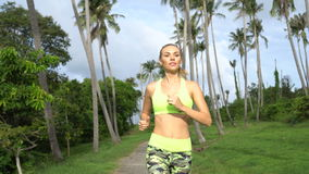 Fitness pretty blonde woman in tropical palm trees garden during beautiful summer day stock footage