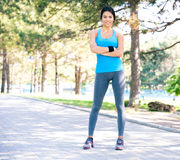 Fitness pretty woman standing with arms folded outdoors Stock Photography