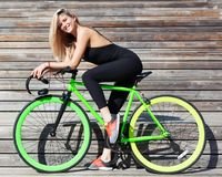 Fitness princess with long hair blondie girl in black skin-tight sexy outfit and sneakers sitting on a green fashion fix. Fitness princess with long hair blond Stock Photos