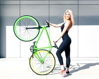 Fitness princess with long hair girl in black sexy outfit and sneakers lifted up vintage green bicycle fix. Outdoor Royalty Free Stock Image