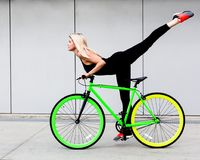 Fitness princess with long hair girl in black sexy outfit and sneakers show trick to fix vintage green bicycle. Outdoor Stock Image