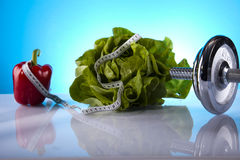 Fitness products. Dumbells, green lettuce and red paprika Royalty Free Stock Photo