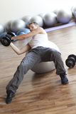 Fitness program, weight lifting on stability ball Royalty Free Stock Photography