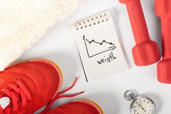 Fitness progress. Top view of notes, towel, red sneakers, barbells and stopwatch Royalty Free Stock Photos