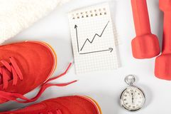 Fitness progress. Top view of notes, towel, red sneakers, barbells and stopwatch Royalty Free Stock Image