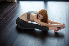 Fitness redhead woman stretching legs Royalty Free Stock Photography