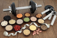 Fitness Regime. Body building equipment with dumbbells and hand grippers with health and super food  including supplement powders, ginseng vitamin pills, pulses Stock Photo
