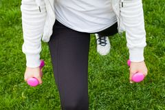 Fitness routine in the park. Young female doing fitness exercises with pink dumbbells in the park, green grass Royalty Free Stock Photos