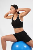 Fitness routine using exercise ball by young woman. Young athletic woman in black sports outfit in her fitness routine using blue exercise ball. Studio shot Stock Image