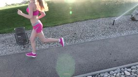 Fitness routine for women - athletic girl runner jogging along road wide angle. Slow motion stock video footage
