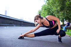 Fitness routine. A young woman stretching her leg muscles Stock Images