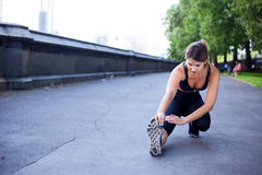 Fitness routine. Young woman stretching her leg muscles Stock Image
