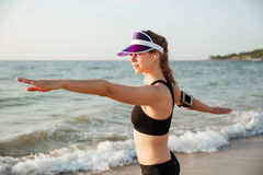 Fitness runner doing warm-up routine on beach before running. Female young fitness runner doing warm-up routine on beach before running Stock Photography