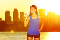 Fitness runner drinking water after city running. In Montreal. Female athlete at urban skyline enjoying sun and drink from water bottle after exercising outdoor stock photography