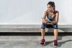 Fitness runner girl using music mobile phone app. Fitness runner on mobile smart phone app tracking progress listening to music with earphones for fitness royalty free stock photo