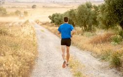 Man running at sunset on country road lane. Fitness runner running extreme cross country and training on rural track jogging at sunset with harsh sunlight and Royalty Free Stock Images