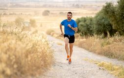 Man running at sunset on country road lane. Fitness runner running extreme cross country and training on rural track jogging at sunset with harsh sunlight and Stock Photography