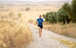 Man running at sunset on country road lane. Fitness runner running extreme cross country and training on rural track jogging at sunset with harsh sunlight and Royalty Free Stock Image