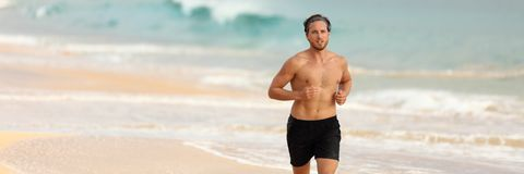 Fitness runner running topless on beach banner. Man athlete running topless in shorts on beach at sunset. Male fitness runner training cardio alone. Banner of royalty free stock photos