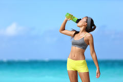 Fitness runner woman drinking water sport bottle. Fitness runner woman drinking water or energy drink of a sport bottle. Athlete girl taking a break during run stock images