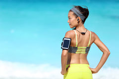 Fitness runner woman with fit back wearing phone armband and wireless headphones. On ocean background. Multiracial exercise girl jogging on summer beach with Royalty Free Stock Image